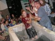 A mother cheers as her daughter is baptized by the youth pastor within a contemporary baptism setting in the youth meeting facility at Bridges Community Church in Fremont, California.