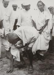 English: Gandhi at Dandi, South Gujarat, picking salt on the beach at the end of the Salt March, 5 April 1930. Behind him is his second son Manilal Gandhi and Mithuben Petit. Français : Gandhi at Dandi, sud du Gujarat, ramassant du sel sur la plage le 5 a