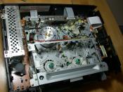 The insides of a video cassette recorder or VCR. (We took it apart to get the tape out and successfully reattached a button that had popped off the front bezel.)