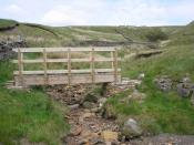 English: Footbridge at Lambfold Gill. This smart new footbridge is part of the restoration work done on the old road known as The High Way. In most weather conditions the bridge is not needed.