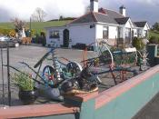 English: Agricultural implements at Drumyouth. The owner of this bungalow runs a little business on the side, buying up old farm implements, painting them in bright colours and selling them on as garden ornaments.
