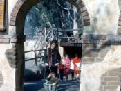 El Camino Real adobe arch entrance portal and rental stroller.