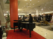 Piano player Joseph Rojo playing at Nordstrom department store, Seattle, Washington. Live piano music at the holiday season is a longstanding Nordstrom tradition.