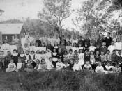English: Students at Moore, Queensland. Group portrait of schoolchildren at Moore, possibly at Moore State School. The students are arranged in four rows. The smaller children sit on the grass in the first row. Psrt of the school buildings, trees and a bu