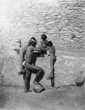Four Hopi Indians (1 adult and 3 children), wearing little or no clothing eating out of bowl next to stone structure.