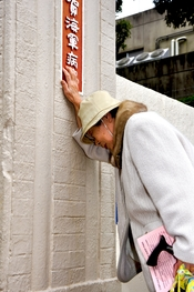 US Navy 101123-N-9023M-003 Hatsue Sugimoto reflects on emotional memories of World War II while touching the historic nameplate