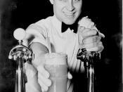 English: Soda jerk passing ice cream soda between two soda fountains.