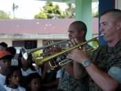 US Navy 070703-N-1752H-083 Sgt. Mark Adams and Cpl. Bobby Sullivan, of the Marine Corps Pacific Band, perform for the local children during medical-dental civic affairs programs held at Tabaco Elementary School