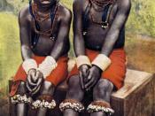 """English: Gewgaws of primitive society. Nigerian maids waiting the signal to perform certain rites in a tribal ceremony. Their bracelets are of hippo ivory, anklets and garters of cowries, and necklaces and """"coronets"""" of long red beads."""
