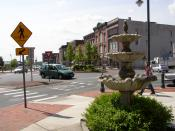 English: Centennial Circle roundabout in downtown Glens Falls, New York, with sidewalk fountain in foreground. Taken from corner between Ridge & Glen Streets, facing southwest.