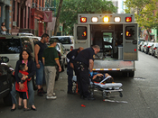 English: A woman collapsed on 7th Street in the East Village when she was with her family. Emergency Medical Technicians arrived and took her to the hospital as her mother and son stand nearby hugging.