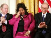 English: Queen of Soul Aretha Franklin wipes a tear after being honored with the Presidential Medal of Freedom Wednesday, Nov. 9, 2005, during ceremonies at the White House. Looking on are fellow recipients Robert Conquest, left, and Alan Greenspan.