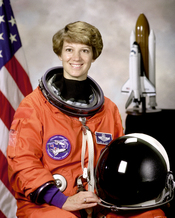 English: STS-93 Commander, Eileen M. Collins shown wearing an orange Launch and Entry Suit (LES) with helmet. Collins was the first woman to command a Space Shuttle mission.