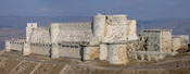 Krak des Chevaliers in Syria. It is an 11th century castle and was used in the Crusades. It was one of the first castles to use concentric fortification, ie: concentric rings of defence that could all operate at the same time. It has two curtain walls and