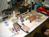 English: This picture shows a table covered with tools for a theatre makeup artist.