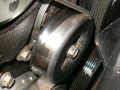 Tensioner in place on a model year 1999 7.4L automotive engine, tensioning the serpentine belt.