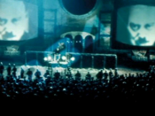 Big Brother's face looms on giant telescreens in Victory Square in Michael Radford's 1984 film adaptation of George Orwell's Nineteen Eighty-Four.